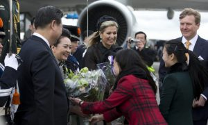 Chinese President Xi Jinping (L) and his wife Peng Liyuan (2nd-L) receive flowers as they are greeted by Dutch King Willem Alexander (R) and his wife Queen Maxima (C) upon arrival at Schiphol airport in Amsterdam on March 22, 2014 ahead of the March 24-25 Nuclear Security Summit (NSS) in The Hague. AFP PHOTO/POOL/PETER DEJONG
